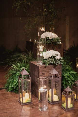 ceremony-decor-with-candles-in-lanterns-ferns-and-white-flowers