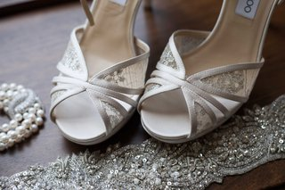 lace-jimmy-choo-high-heels-sitting-next-to-a-delicate-pearl-necklace