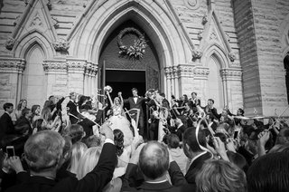 black-and-white-photo-of-bride-and-groom-celebrating-after-wedding-ceremony-in-cathedral