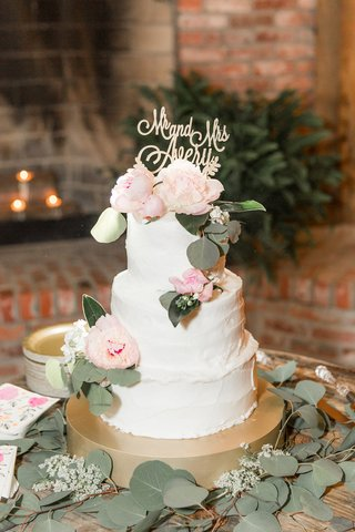 white-wedding-cake-made-by-the-bride-on-gold-stand-fresh-peony-flowers-and-eucalyptus-silver-dollar