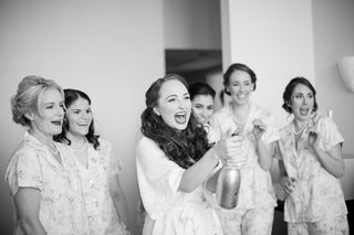 black-and-white-photo-of-bride-popping-champagne-bridesmaids-getting-ready-wedding-fun