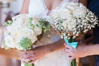 brides-bouquet-of-white-flowers-and-touches-of-green-bridesmaid-bouquet-of-babys-breath-roses