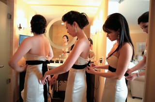 bridesmaids-in-strapless-cream-gowns-with-black-sashes