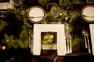 wedding-reception-place-setting-with-a-square-charger-napkin-and-orchid