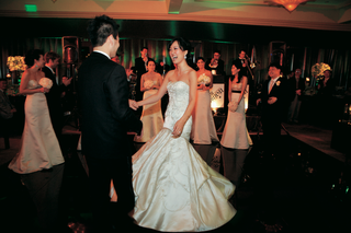 bride-in-a-fit-and-flare-lazaro-gown-and-groom-in-a-black-tuxedo-on-the-dance-floor