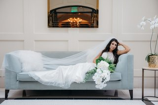 bride-in-maggie-sottero-wedding-dress-with-silver-beading-lounges-on-slate-blue-couch-cathedral-vei
