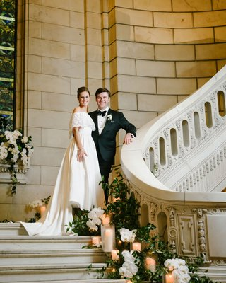bride-in-mothers-wedding-dress-groom-in-tuxedo-on-staircase-greenery-pillar-candles-white-flowers