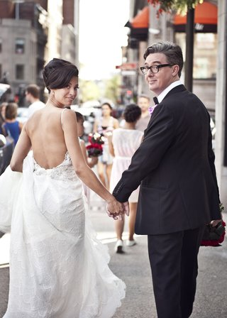 bride-in-pnina-tornai-lace-wedding-dress-open-back-groom-with-glasses-look-back-while-walking