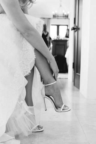 black-and-white-photo-of-bride-fastening-stuart-weitzman-heel