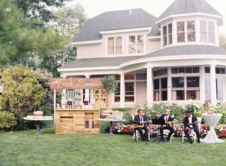 marriott-family-lake-house-with-fresh-lemonade-wood-stand-musicians-in-chairs-ice-tea