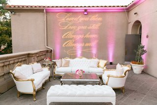 vow-renewal-anniversary-party-lounge-area-with-gold-white-furniture-and-projected-sign-on-wall