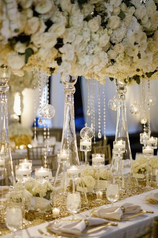 wedding-reception-table-with-tall-centerpiece-of-white-hydrangeas-roses-orchids-floating-candles