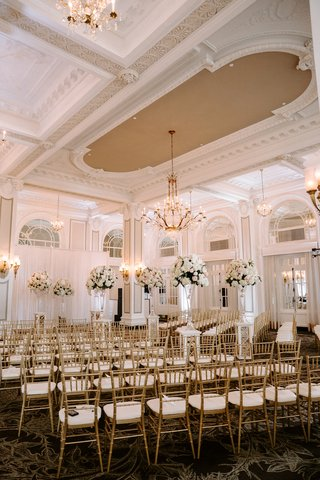 ornate-molding-at-ballroom-in-atlanta-gold-chairs-tall-flower-arrangements-along-aisle-white-drapery