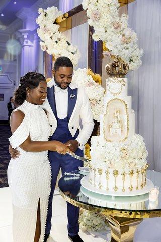 bride-in-second-wedding-dress-and-groom-cutting-wedding-cake-gold-white-castle-design-flower-garland