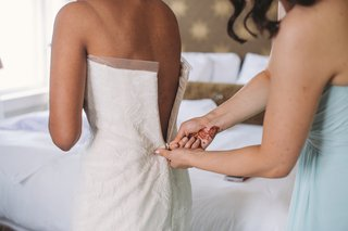 women-with-henna-on-hands-helping-bride-put-on-gown