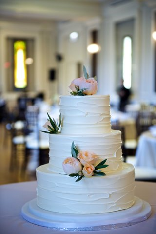 white-wedding-cake-with-stucco-frosting-siding-peach-garden-rose-and-green-leaf-decorations