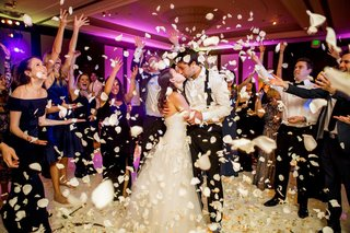 wedding-reception-bride-and-groom-kiss-guests-tossing-white-rose-flower-petals-purple-pink-lighting