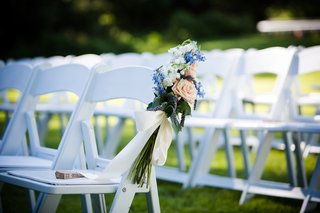 white-folding-chairs-with-bouquet-tied-on-end