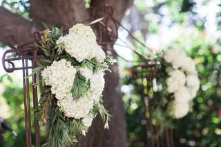 garden-wedding-ceremony-with-metal-arch-white-hydrangeas-and-greenery