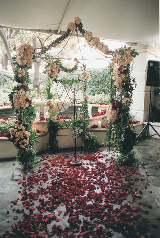 flower-wedding-arch-in-front-of-fountain-with-red-rose-aisle