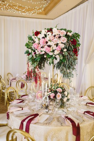 round-tablescape-champagne-hued-linen-tall-centerpiece-patterned-pink-red-white-flowers-low-candles