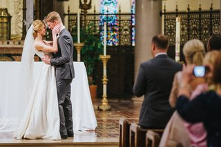 bride-in-custom-a-line-gown-and-chapel-veil-groom-in-grey-suit-bride-and-groom-about-to-kiss
