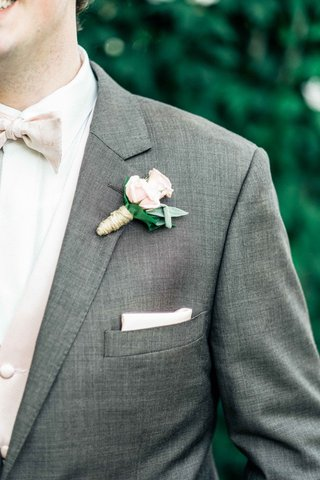 groom-in-gray-tuxedo-with-a-light-pink-bow-tie-and-a-light-pink-and-green-boutonniere