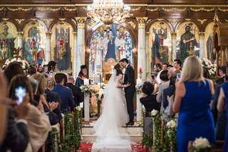 wedding-ceremony-greek-orthodox-cathedral-gold-foil-chandelier-greenery-church-pews