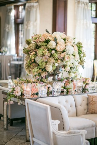 flowers-white-and-blush-flowers-on-mirror-table-with-candles-and-lounge-furniture-tufted-sofa