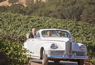 bride-and-father-of-bride-being-escorted-to-ceremony-space-in-classic-white-car-convertible