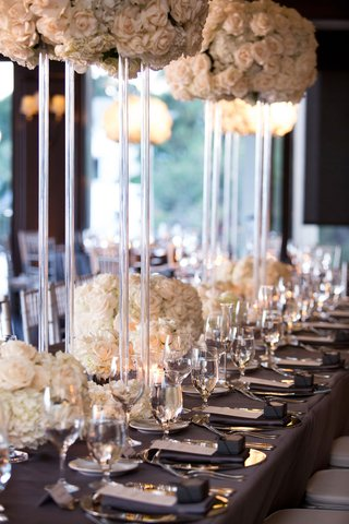 wedding-reception-long-table-dark-grey-linen-tall-lucite-acrylic-riser-white-flowers-low-flowers