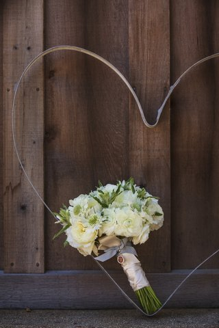 brides-bouquet-of-white-flowers-with-greenery-bound-by-white-ribbon-against-wood-barn-door