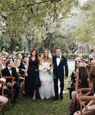 bride-with-mother-of-bride-and-father-of-bride-in-navy-blue-wood-chairs-grass-aisle-outdoor-ceremony