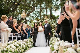 bride-in-monique-lhuillier-wedding-dress-walks-down-aisle-with-mother-of-bride-and-father-of-bride