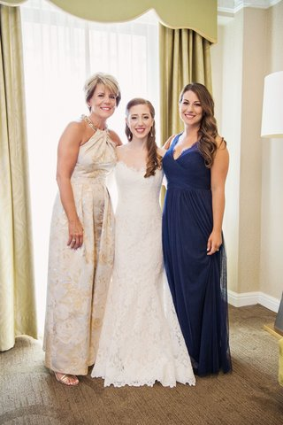bride-in-romona-keveza-wedding-dress-with-sister-bridesmaid-and-mom-in-halter-gown-gold-flowers
