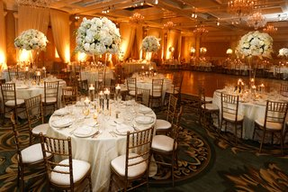 wedding-reception-with-draping-warm-lighting-centerpieces-of-white-hydrangeas-roses-orchids