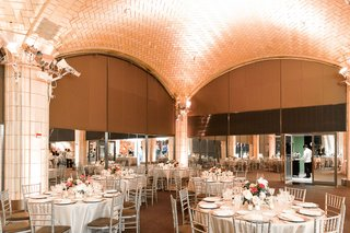 wedding-reception-tall-arches-new-york-city-round-tables-silver-chairs-low-centerpieces