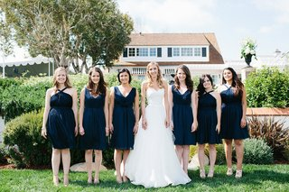 bride-in-white-wedding-dress-with-bridesmaids-in-short-navy-blue-bridesmaid-dresses