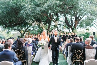 wedding ceremony recessional couple a line gown with veil and overskirt gold garden chairs trees