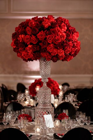wedding-reception-decor-round-table-tall-crystal-centerpiece-red-flowers-roses-black-guest-chairs