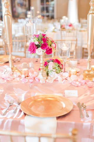 wedding-reception-table-pink-linen-gold-charger-white-napkin-floating-candles-low-pink-rose-flowers