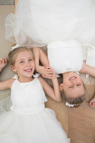 adorable-flower-girls-in-white-dresses-with-tulle-skirts-lying-down-head-to-head-while-holding-hands