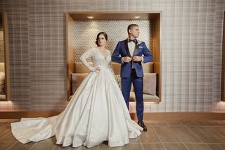 bride-in-long-sleeve-pnina-tornai-ball-gown-wedding-dress-groom-in-navy-tuxedo-bow-tie-pose-portrait