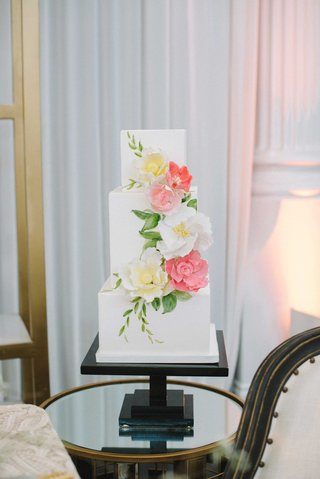 a-square-cake-with-three-tiers-featuring-white-yellow-and-pink-floral-detailing