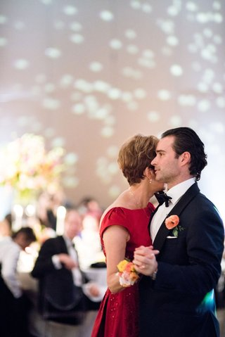 groom-in-tuxedo-and-bow-tie-dancing-with-mother-of-groom-in-red-dress-corsage