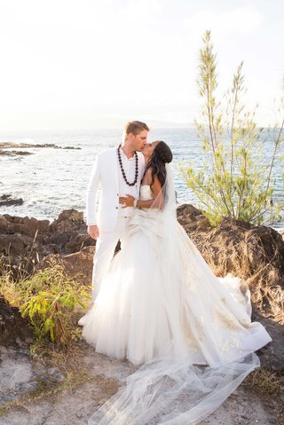 joshua-faulkner-in-white-suit-with-kukui-nut-shell-lei-and-chudney-ross-in-lazaro-wedding-dress-gold