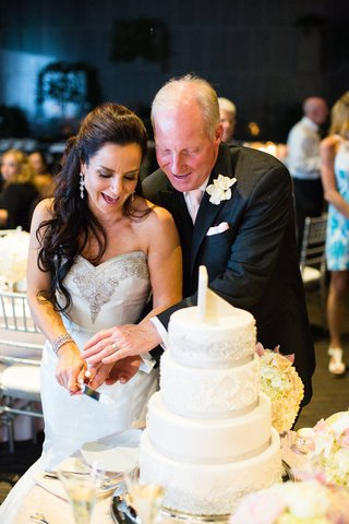 bride-and-groom-smile-in-wedding-gown-black-tuxedo-pink-tie-cutting-white-cake