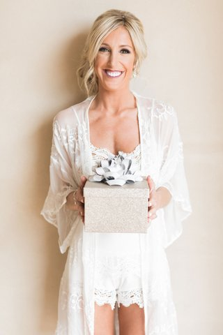 bride-in-getting-ready-robe-holding-gift-box-with-big-ribbon-low-bun-white-romper-and-robe