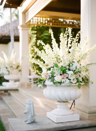 garden-wedding-reception-with-large-urn-filled-with-white-and-pink-flowers-and-greenery