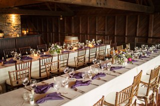 long-kings-tables-at-winery-vineyard-wedding-reception-indoor-dinner-wood-chairs-purple-napkins